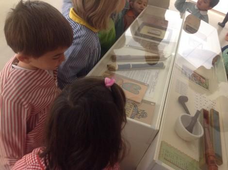 Niños y niñas observando una vitrina con objetos de Aurelio Suárez.
